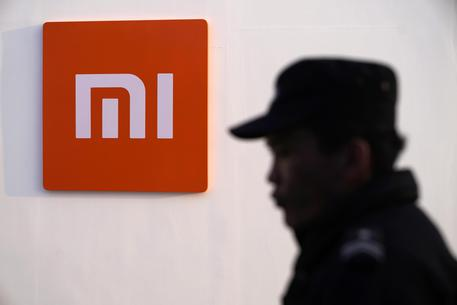epa07382403 A security guard stands beside a logo of Xiaomi during the Xiaomi product launch ceremony in Beijing, China, 20 February 2019. Xiaomi releases its new mobile phone products 'Mi 9', 'Mi 9 Explorer Edition' and 'Mi 9 SE' on 20 February 2019. EPA/WU HONG